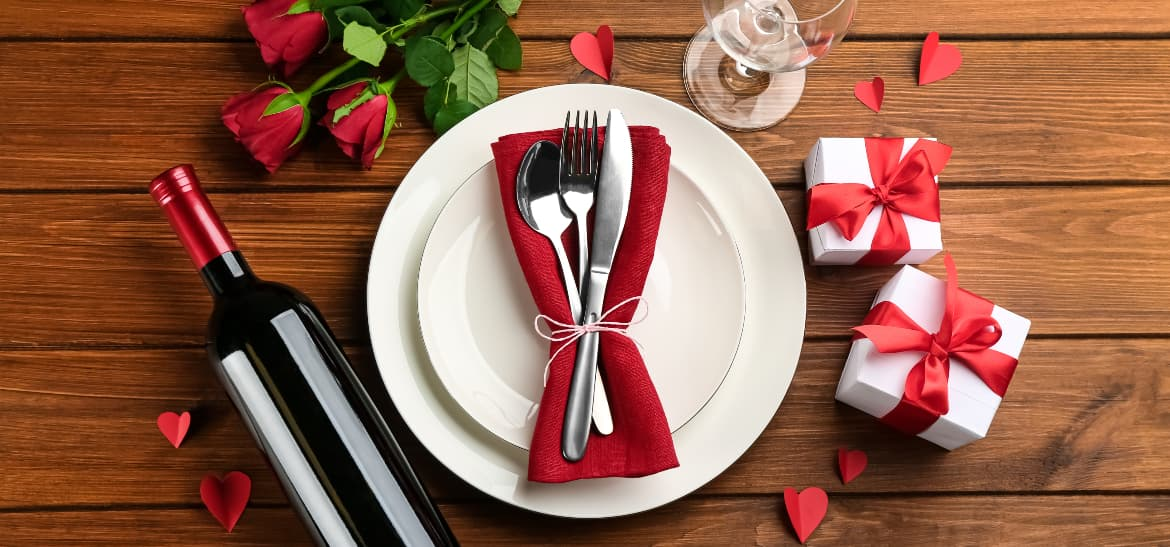 Plate with silverware, bottle of red wine, and hearts